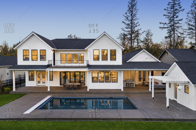 Modern farmhouse luxury home exterior with in ground pool at twilight