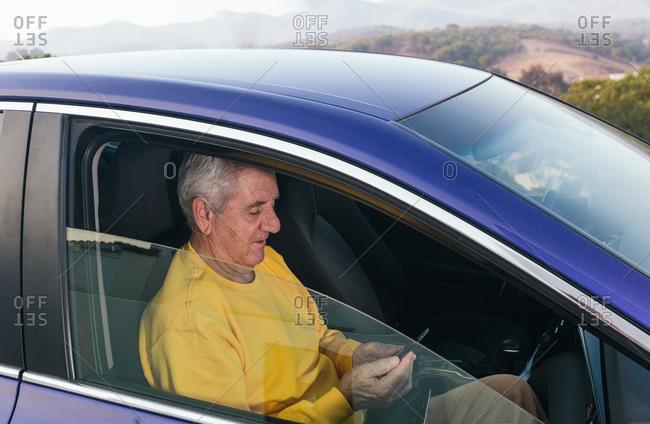 Positive elderly male traveler suing smartphone in car