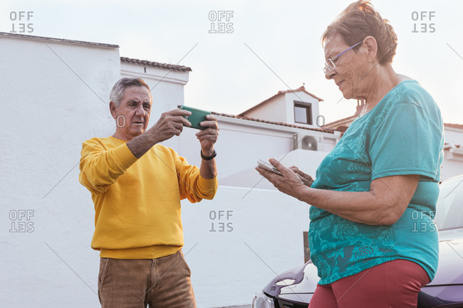 Senior couple using smartphones near car