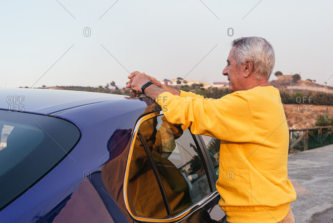 Elderly male resting near car in countryside