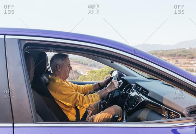 Senior man driving car in countryside