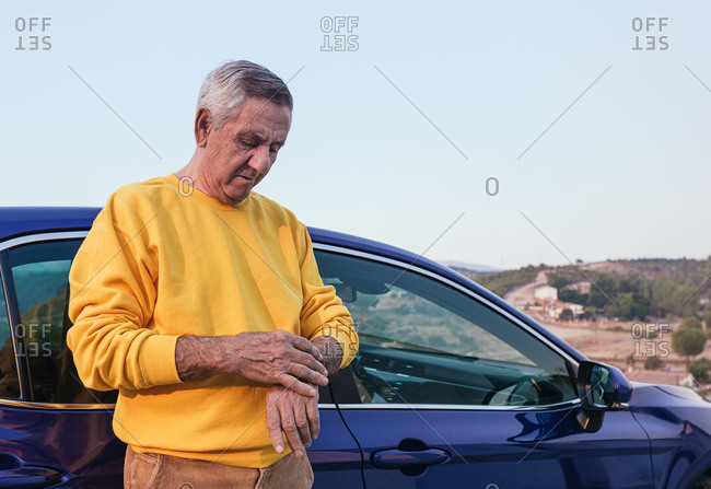 Aged traveler checking time near car