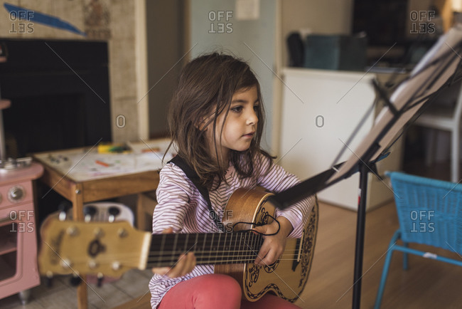 6 yr old girl with dark hair practicing guitar lesson in playroom
