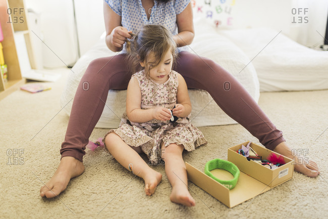 Barefoot mom sitting on bed braiding young daughter's hair