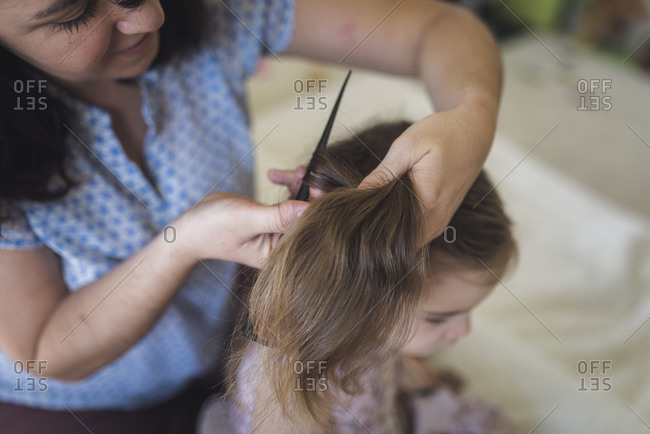 Mother wearing blue shirt putting 4 yr old's hair into ponytail