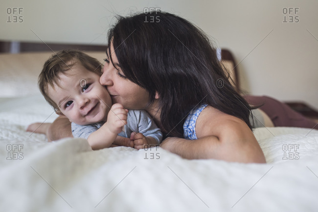 Loving mother kissing sweet smiling baby while lying on bed