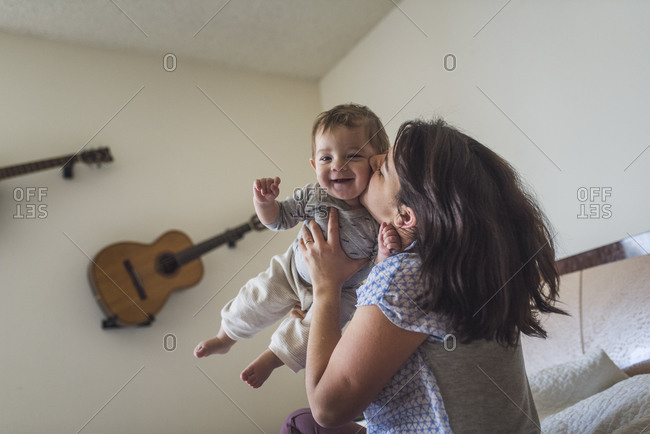 Mother kissing smiling barefoot baby in bedroom with guitars on wall