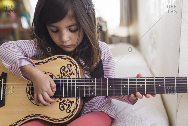 Serious 6 yr old girl picking guitar string while sitting on bed