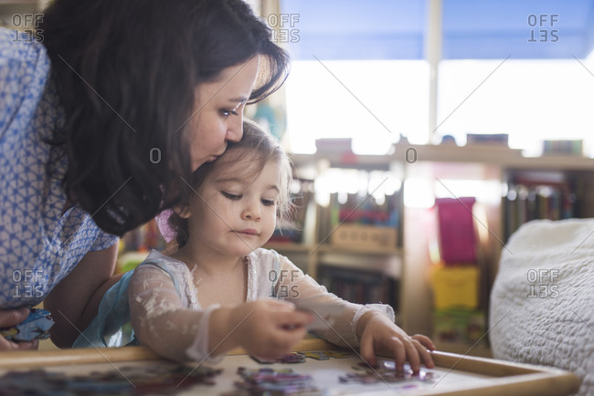 Mid-30's mom kissing head of 4 yr old daughter putting puzzle together