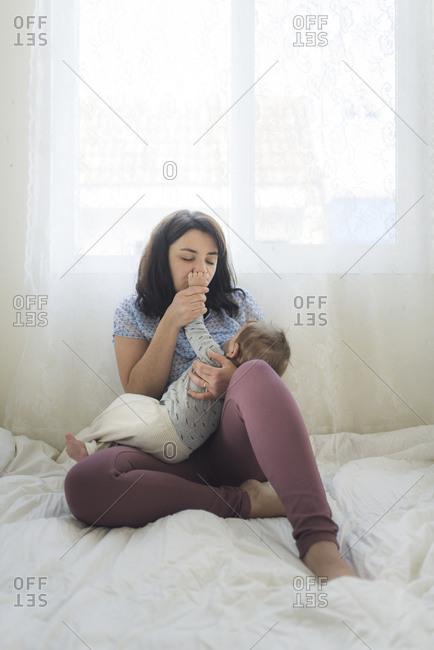 Mid-30's mom with closed eyes kissing hand of baby while breastfeeding