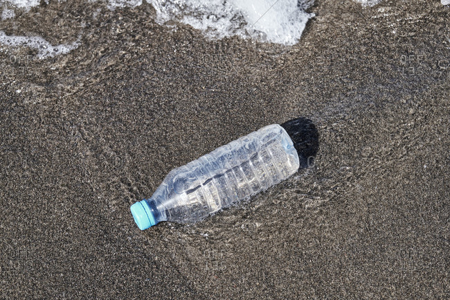 Single-use plastic bottle floating in the sea