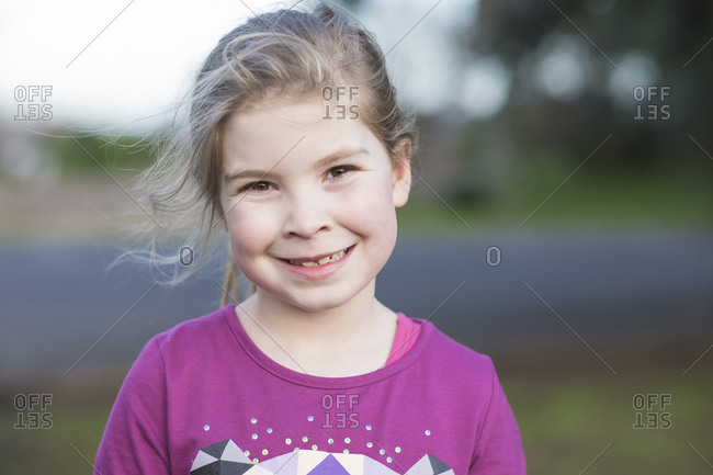 Closeup portrait of a young girl standing and smiling at the camera