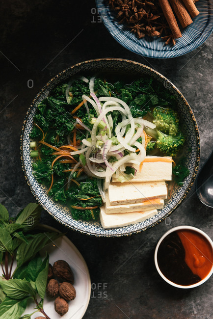 A bowl of vegetarian and tofu Pho with raw ingredients and spices