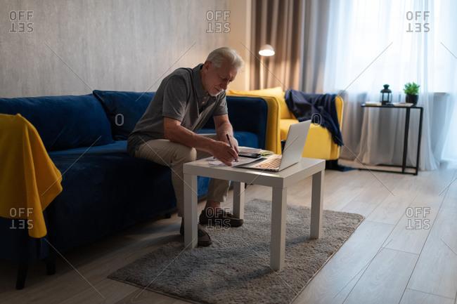 Senior man checking bills at home