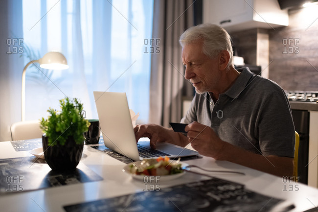 Aged man using laptop for online shopping