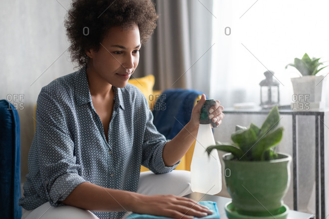 Black housewife spraying potted plant