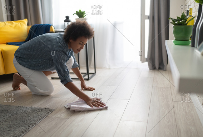 Ethnic woman washing floor at home