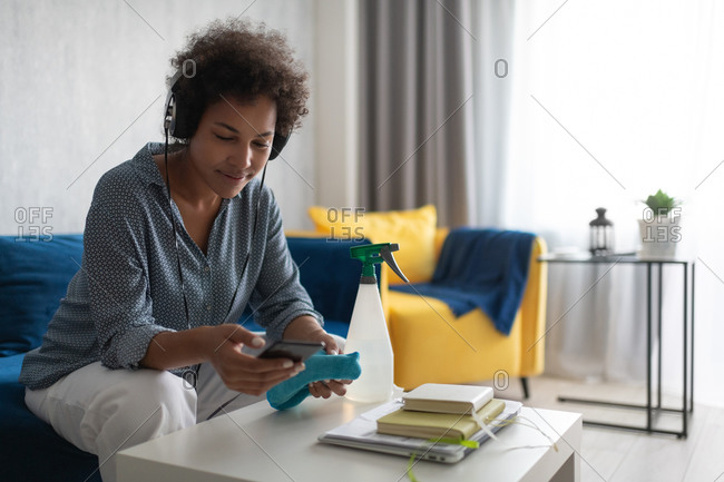 Black housewife in headphones using smartphone