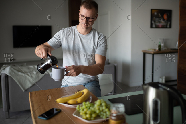Adult male pouring tea in morning