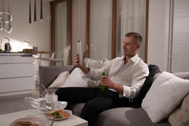 Businessman with beer making video call