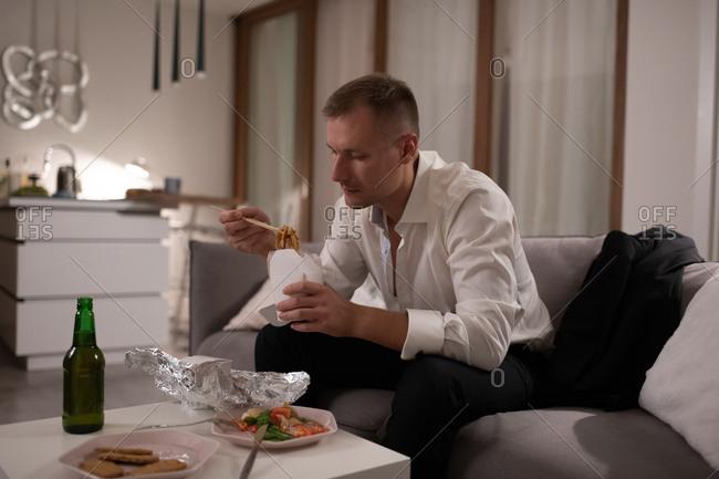 Adult entrepreneur eating noodles for dinner