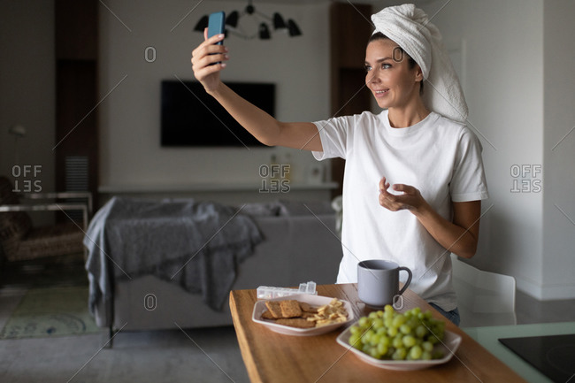 Woman making video call to friends in morning