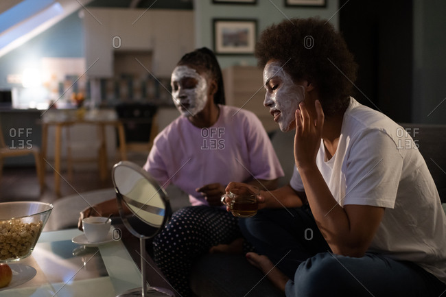 Ethnic woman smearing mask during sleepover