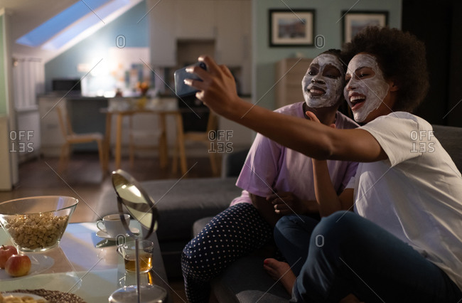 Excited multiethnic girlfriends taking selfie during sleepover