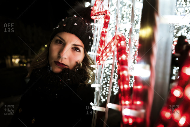 A young girl is posing and looking at the camera next to Christmas lights