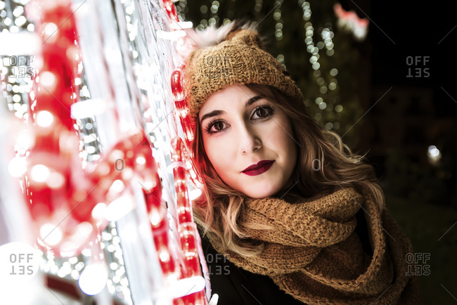A young girl is looking at the camera next to Christmas lights