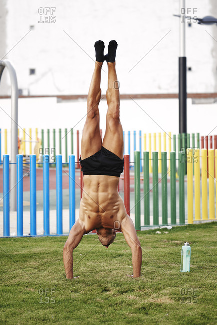 A young and strong man doing calisthenics upside down
