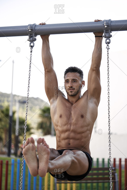 An athletic man training on metal bars in the open air