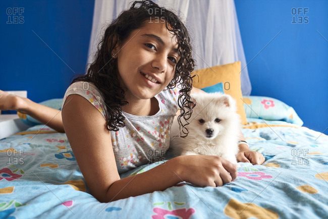 A little girl and her white Pomeranian puppy look into the camera