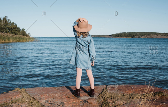 Young girl holding onto her hat whilst looking out at the Finish sea
