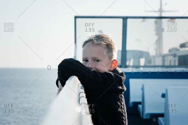 Portrait of a young boy on a ferry looking happy and relaxed at sea