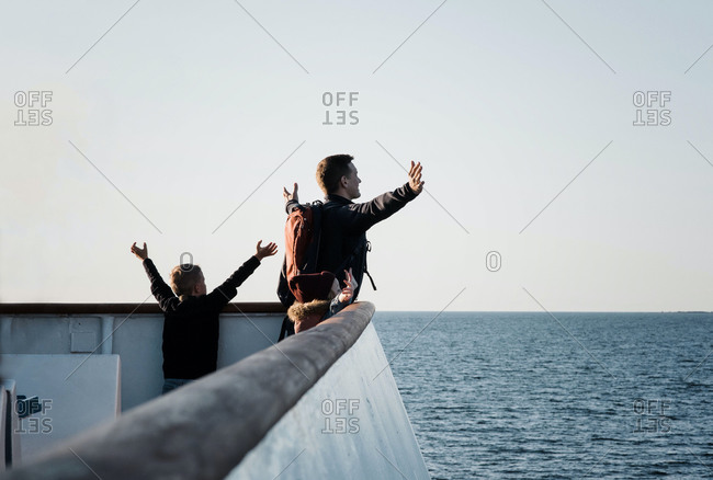 Father and his children playing titanic feeling the breeze on a boat