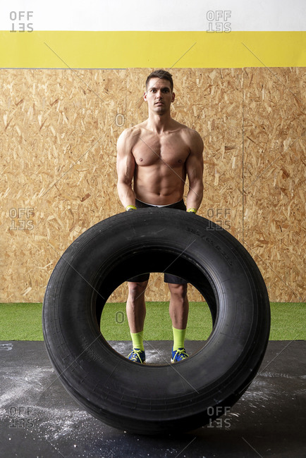 Young muscular man flipping a tire at gym