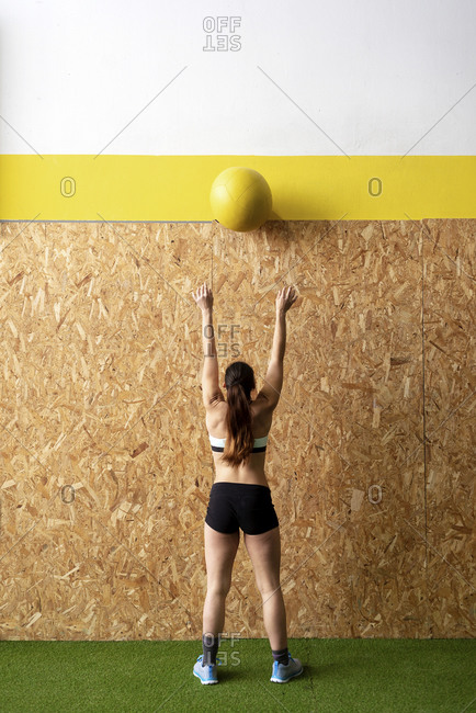Rear view of beautiful young athlete with ponytail throwing up heavy leather ball to cork wall at gym