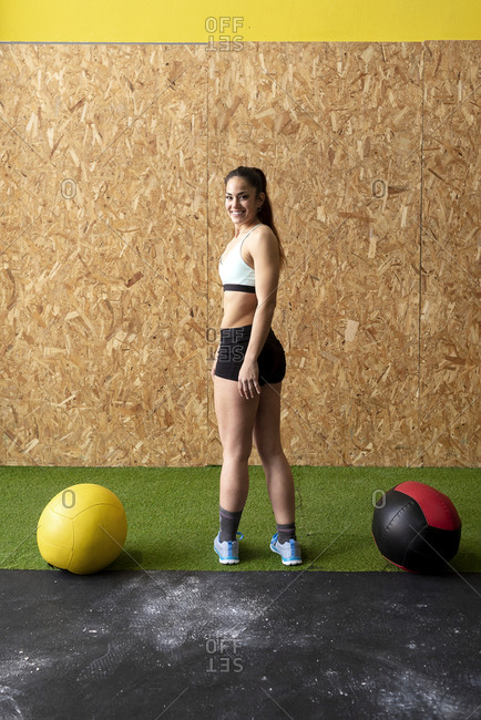 Beautiful smiling young woman in sportswear standing against cork wall with heavy leather balls on ground while looking at camera at gym
