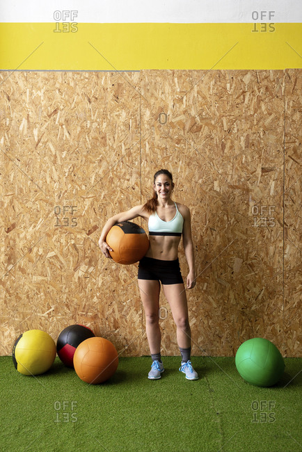 Beautiful smiling young female in sportswear holding heavy leather ball and looking at camera while standing near cork wall at gym