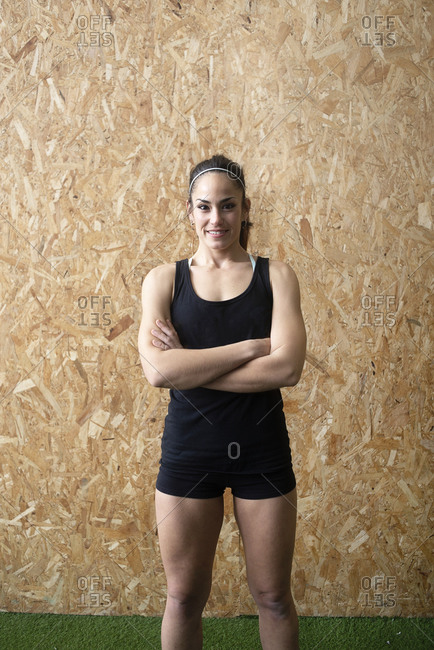Portrait of a beautiful young sports woman with arms crossed standing against cork wall at gym