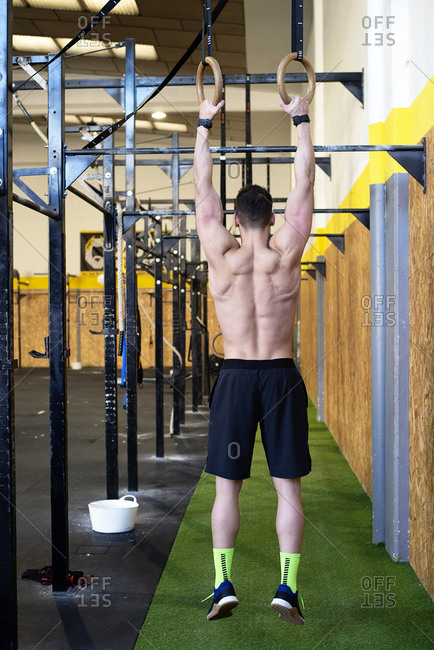 Rear view of fit man training with rings at gym