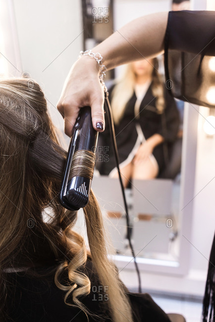 Closeup of hairstylist curling hair woman client in hairdressing beauty salon