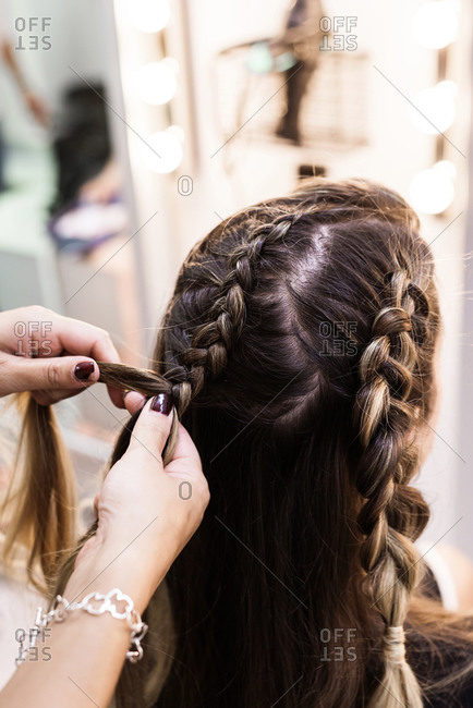Hairdresser making braids to a young client at Hairdresser salon