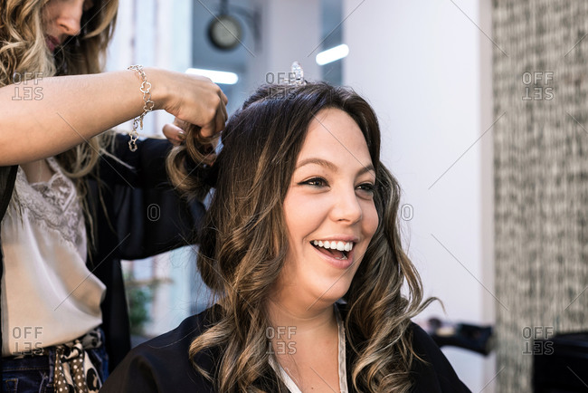 Long haired woman getting haircut at a hairdresser beauty salon