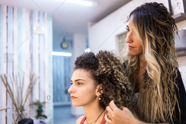 Hairdresser combing client with long curly hair against wall mirror at hair salon