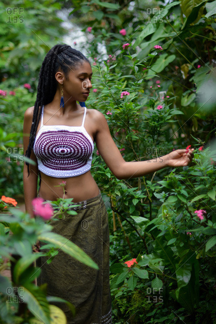 Young afro Colombian woman touches flower in garden