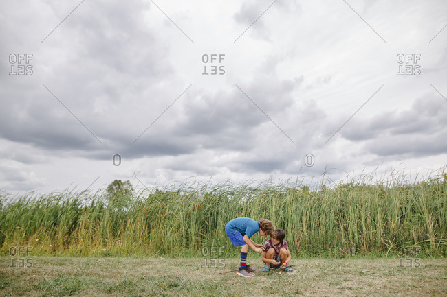 Two boys play together by tall cattails on a cloudy day