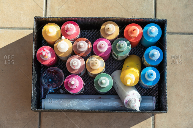 Overhead of various paint colors in a black box on the floor.