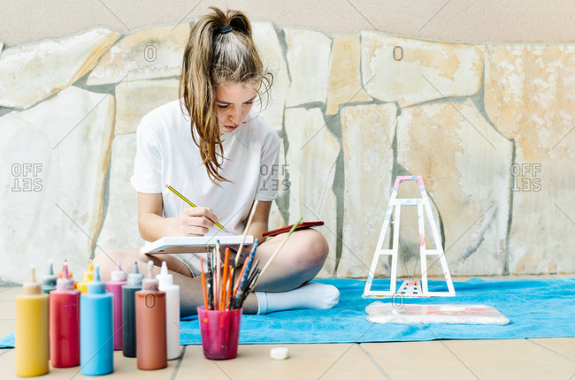 Caucasian girl painting a picture sitting on a terrace with all painting elements around her